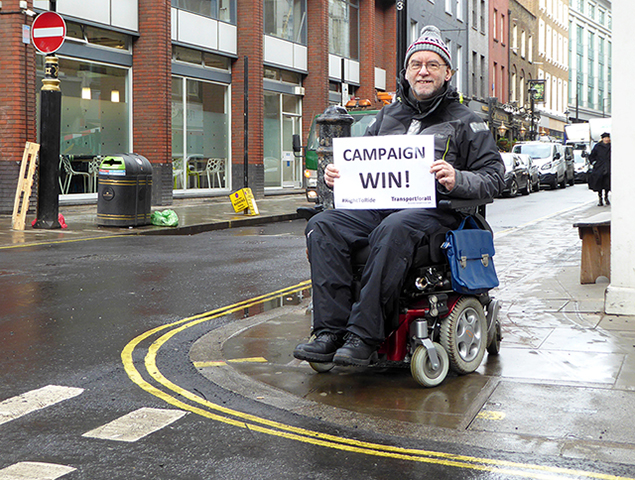 "Picture of Chris posing in Soho, near a brand new kerb drop recently installed by Westminster Council. Chris is on his electric wheelchair, holding a ""Campaign Victory"" sign"