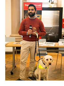 Picture of dr amit patel giving a speech next to his guide dog kika