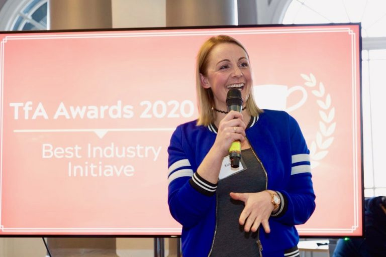 Kirsty, a white woman with blonde hair and wearing a blue jacket, is standing in front of a screen which reads 'TFA Awards 2020' and speaking into a microphone.