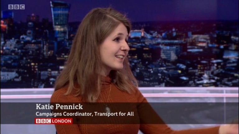 Katie, a white woman with brown hair, in mid-sentence, on BBC London news. There is an aston at the bottom of the screen reading 'Katie Pennick, Campaigns Coordinator, Transport For All'.
