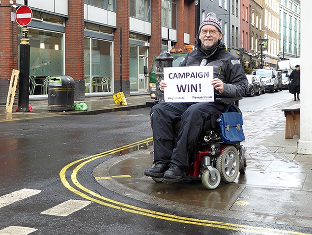 """Picture of Chris posing in Soho, near a brand new kerb drop recently installed by Westminster Council. Chris is on his electric wheelchair, holding a """"Campaign Victory"""" sign"""