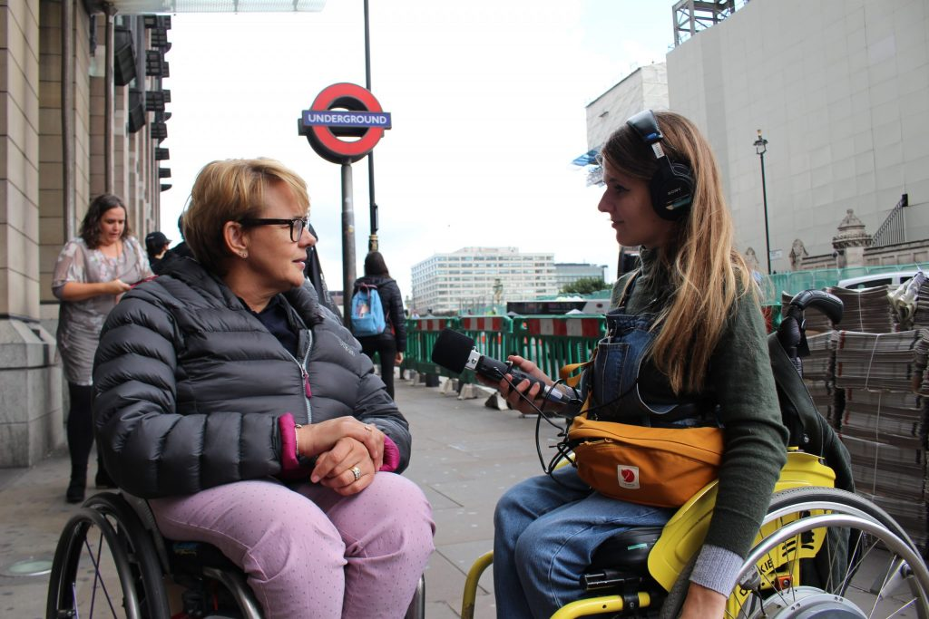 Katie and Tanni, two women sat in their wheelchairs outside a Tube station. Katie is holding a microphone up to Tanni and listening as Tanni speaks.