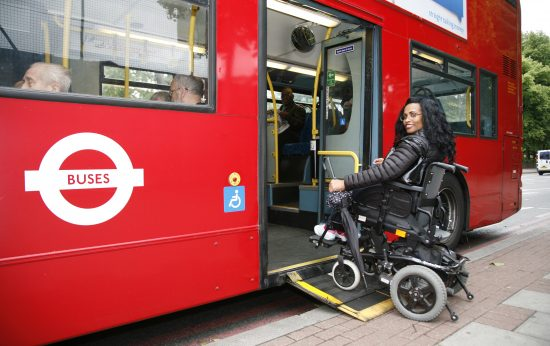 A woman in an electric wheelchair boards a London red bus using the ramp