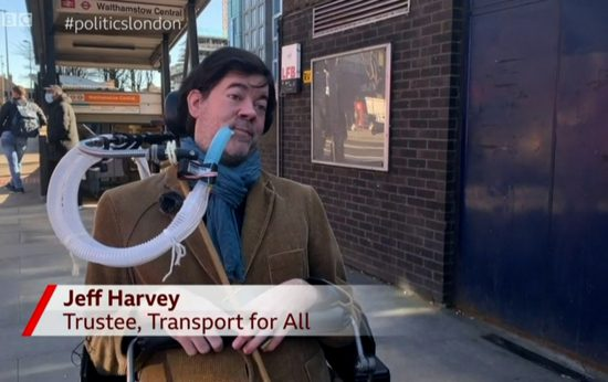 """Jeff, a white man with dark brown hair who is wearing a corduroy blazer and sat in an electric wheelchair using a breathing apparatus, is outside Walthamstow Tube station speaking to the camera about step-free access. The aston reads """"Jeff Harvey, Trustee, Transport For All'"""