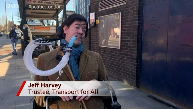 "Jeff, a white man with dark brown hair who is wearing a corduroy blazer and sat in an electric wheelchair using a breathing apparatus, is outside Walthamstow Tube station speaking to the camera about step-free access. The aston reads ""Jeff Harvey, Trustee, Transport For All'"