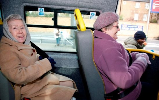 Two elderly women sitting in a dial-a-ride bus