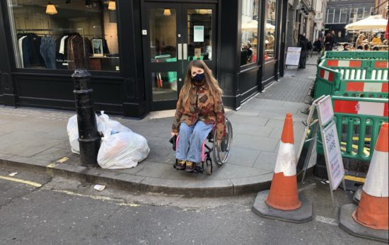 Katie in her wheelchair at the edge of a pavement with no dropped kerbs.