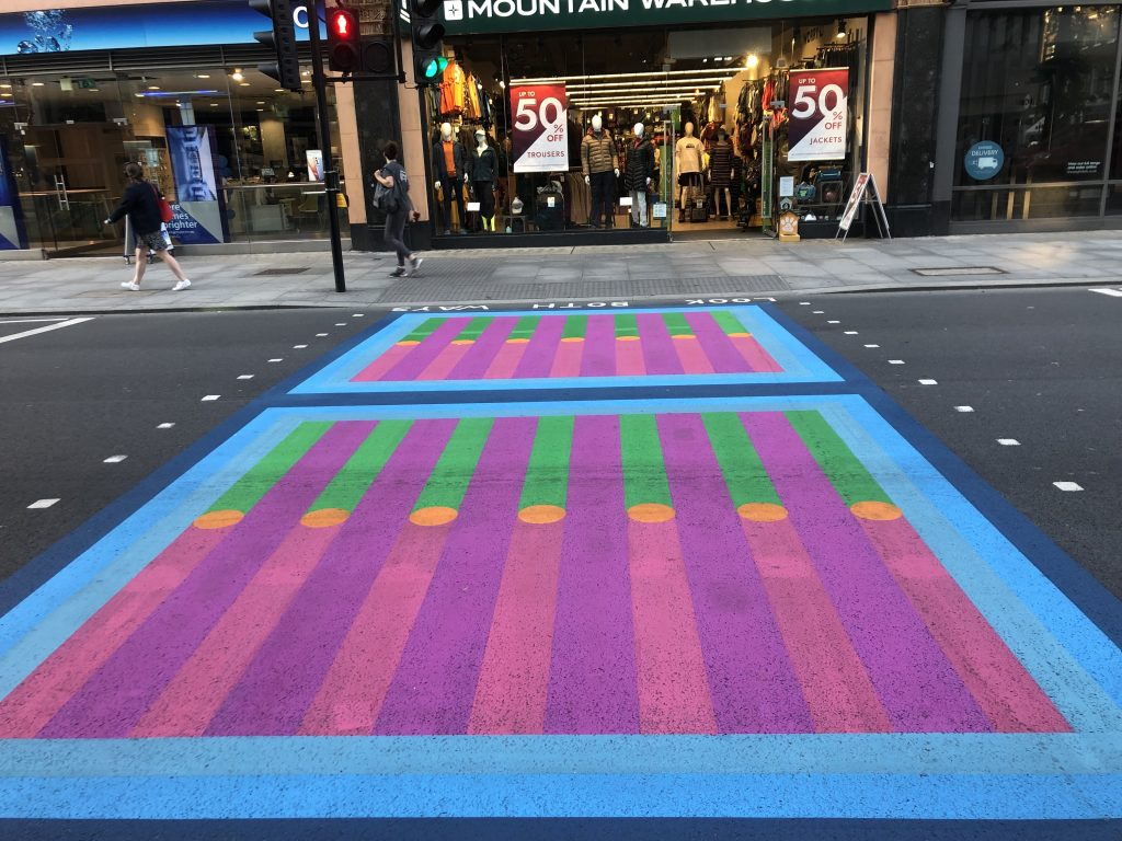 Pedestrian crossing that has been painted over with a brightly coloured geometric pattern